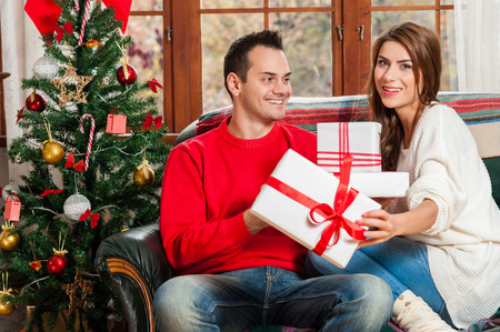 couple on couch: Celebrating Christmas together. Beautiful young couple sitting on the couch and smiling at camera exchanging gifts.