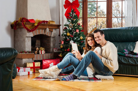 home sale: Celebrating Christmas together. Beautiful young couple sitting on the floor in christmas decorated living room, smiling and watching something on tablet pc.