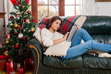 young tree: Young woman sitting on couch, alone, in front of christmas tree on living room,using tablet pc.