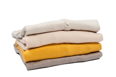 colore: Stack of sweaters nude colore on the white background Stock Photo