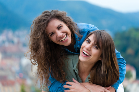 friends hugging: Pretty couple hugging, flirting and laughing. Stock Photo