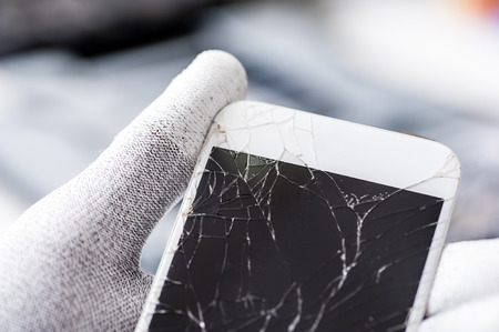 Close-up photo of a smartphone with broken screen.