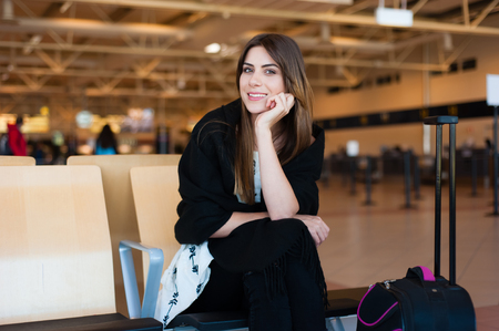 flight: Airport Young female passenger at gate waiting in terminal while waiting for her flight. Stock Photo