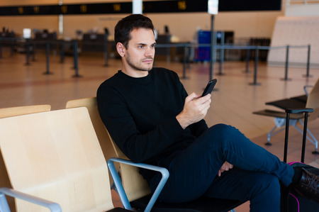 casual wear: Portrait of handsome smiling man in casual wear, with his mobile phone while sitting in the hall of the airport terminal, while waiting for his flight.