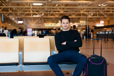 student travel: Portrait of handsome smiling man in casual wear sitting in the hall of the airport terminal, while waiting for his flight.