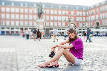 Young woman tourist holding a photo camera and taking picture in Plaza Mayor square, Madrid, Spain. Tourist attraction, statue of Felipe III in the background. Standard-Bild
