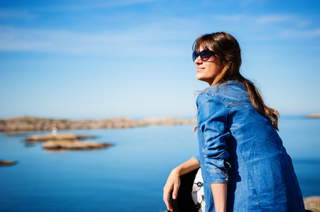 calming: Woman sitting next to a beautiful calming blue sea