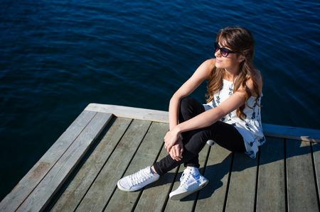 mujer mirando el horizonte: Ni�a sentada en el embarcadero por el mar y mirando hacia el futuro en el d�a de oto�o Foto de archivo