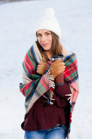 Beautiful girl wrapped in a blanket, in snow, drinking hot drink outdoors.