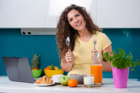playing with spoon: Casual woman eating breakfast and working or catching up on her social media on her laptop as she sits at the dining table at home, while playing with a fork and a spoon.