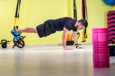 push: Man does cross fit push ups with trx fitness straps in the gyms studio