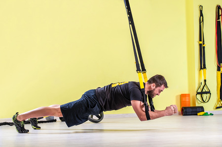 Man does cross fit push ups with trx fitness straps in the gym's studio