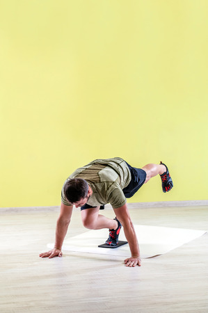 bilateral: Sport young man at gym, exercising with friction pads.