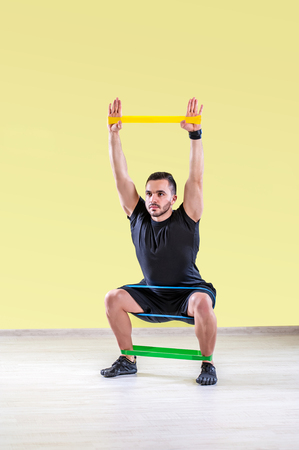 Guy working out with rubber band in studio gym.