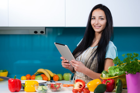 home cooking: Young beautiful woman using a tablet computer to cook in her kitchen