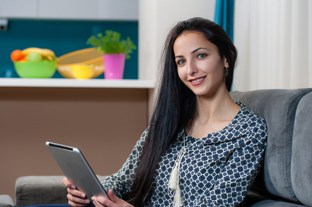 topicality: Smiling young woman laying on couch and using digital tablet, looking at camera
