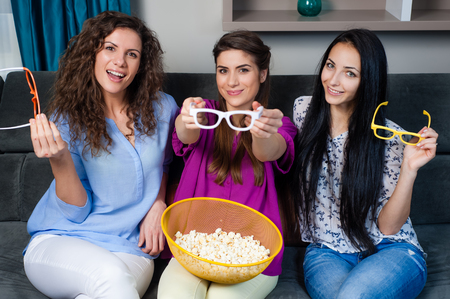 Fun Movie with Girlfriends. Three smiling girls fighting on popcorn while watching a movie on tv with 3d glasses, at home.