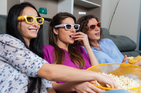 home entertainment: Fun Movie with Girlfriends. Three smiling girls eating popcorn while watching a movie on tv with 3d glasses, at home