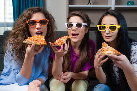 Fun Movie with Girlfriends. Three smiling girls eating pizza while watching a movie on tv with 3d glasses, at home.