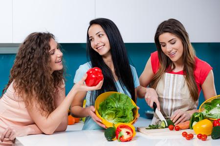 mujeres cocinando: Jóvenes tres amigos de la mujer que cocina en la cocina y que se divierten, chica hablando y riendo. cortar las verduras en una tabla de cortar Foto de archivo