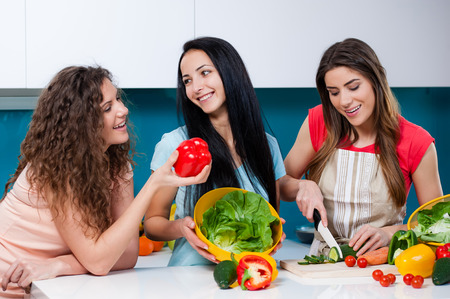 Young three woman friends cooking in the kitchen and having fun, girl talking and laughing. cutting vegetables on a cutting board 版權商用圖片