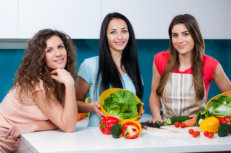 friends fun: Young three woman friends cooking in the kitchen and having fun, girl talking and laughing. cutting vegetables on a cutting board Stock Photo