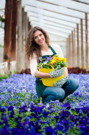 big flower: Young woman in a colorful flower garden in a greenhouse with a big flower pot.