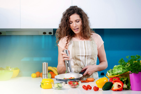 kitchen aprons: Young woman cooking healthy food, pouring salt in a pan with vegetables in it.