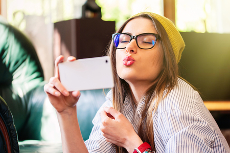 Pretty hipster girl taking selfie and making duck face.
