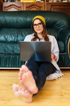 Hipster woman sitting on the floor using a laptop