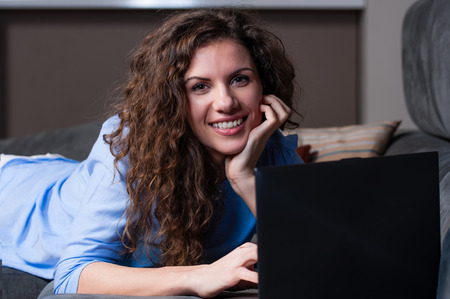 Smiling young woman laying on couch and using laptop, looking at camera.