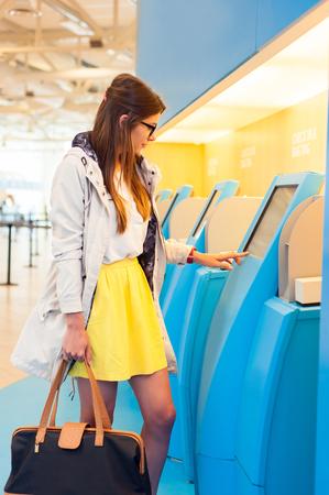 Mujer joven en el área de transferencia de autoservicio haciendo auto-check-in en la máquina automatizada con pantalla táctil en el edificio terminal del aeropuerto Foto de archivo