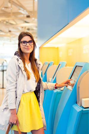 Young woman at self service transfer area doing self-check-in at automated machine with touchscreen display in airport terminal building Stock Photo
