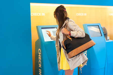 Young woman at self service transfer area doing self-check-in at automated machine with touchscreen display in airport terminal building Stock fotó
