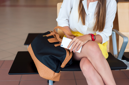 body parts cell phone: Body parts close-up. Young woman holding her cell phone while sitting, waiting to board a plane at the departure gates. Stock Photo