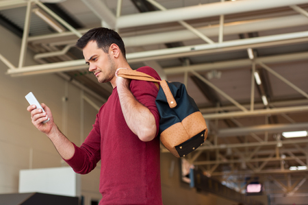 Portrait of handsome man in casual wear holding his luggage and messaging through his mobile phone while walking in the hall of the airport