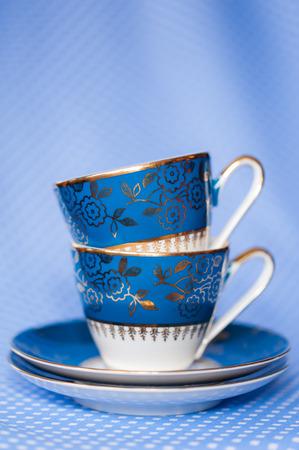 Stapel von antiken Tassen Tee auf blauem Hintergrund