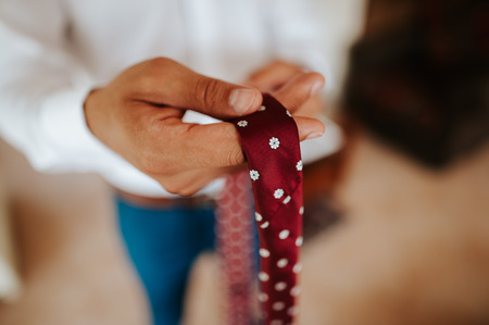 Close-up of a businessman holding a tie.