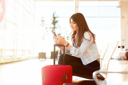 Toevallige jonge vrouwenzitting die haar celtelefoon met behulp van terwijl het wachten om een ??vliegtuig bij de luchthaven eindwachtkamer in te schepen. Stockfoto