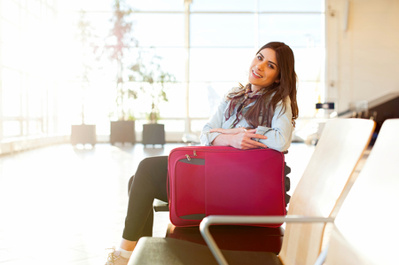 Woman smiling, waiting her flight at airport terminal, sitting, in waiting room with her trolley bag. Stock Photo