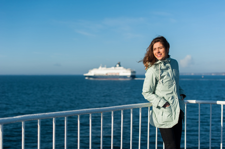 Young traveller woman looking the sea, sailing a ferry, with big boat cruise liner or ferry on the background, wearing a rain jacket.