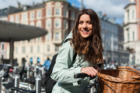 Young happy woman on bicycle looking at camera and smiling in the city of Copenhagen, Denmark. Activity, healthy lifestyle and environmentally friendly transport