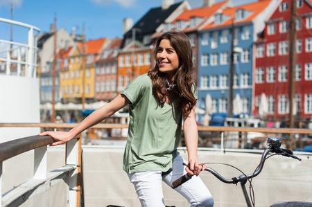 素敵な若い女性が晴れた日に自転車でヨーロッパの都市コペンハーゲン、デンマークのニューハウン港桟橋でポーズします。スカンジナビア、ヨー 写真素材