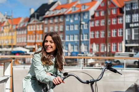 Young happy woman on bicycle at the Nyhavn harbor pier in european city Copenhagen, Denmark, looking at camera and smiling. Visiting Scandinavia, famous European place. Stockfoto