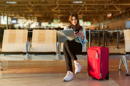 Airport Young female passenger on smart phone and laptop sitting in terminal hall while waiting for her flight Stockfoto