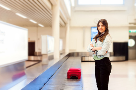 Young woman passenger in 20s waiting her luggage at conveyor belt in arrivals lounge of airport terminal building