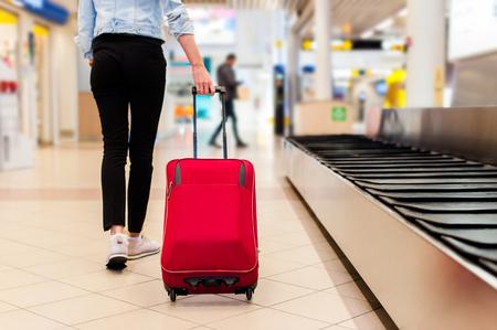 Close-up van jonge vrouw in het transportband gebied met haar trolley tas.