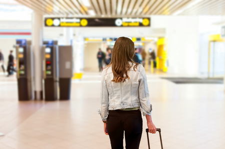 Close-up of young woman back side at the airport, carrying her trolly bag. Stock Photo