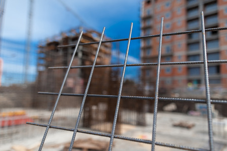 Reinforcement net of concrete in the construction site, metal rods for strength with a building under construction on the background Stock Photo
