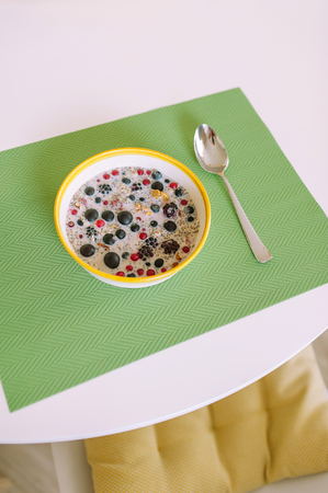 Top view of round table with a bowl of cereals and spoon with white copy space ,chair and pillow.